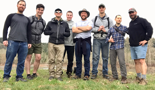 Group of men taking picture in open field.