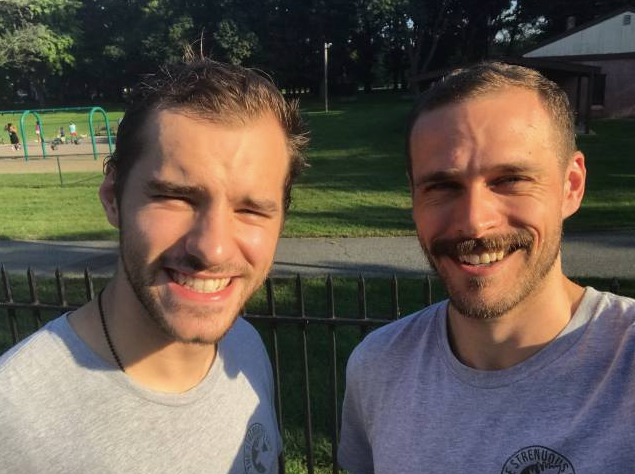 Two young men smiling on a sunny day.